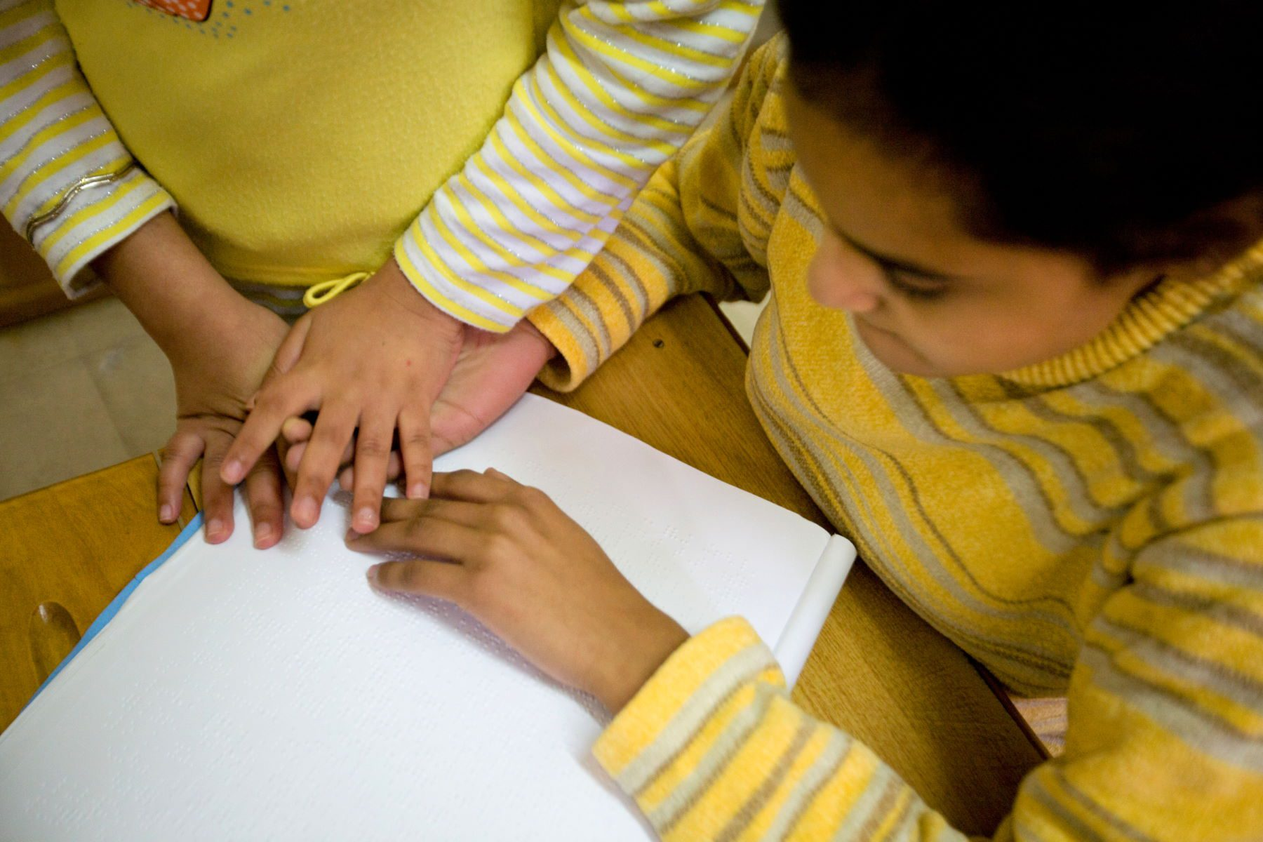 two children clasp hands while they study in a home in Alexandria, Egypt.