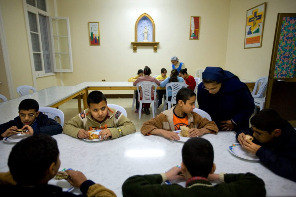 a nun talks to a children seated at a lunch table in Alexandria.