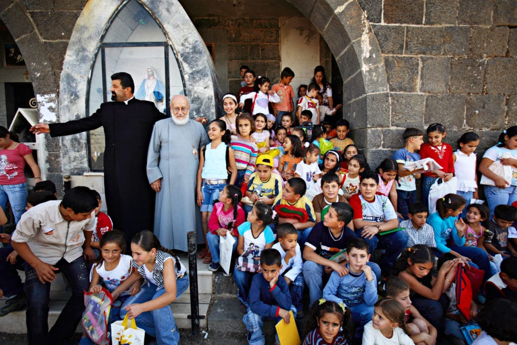 a bishop meets with a group of schoolchildren in Syria.