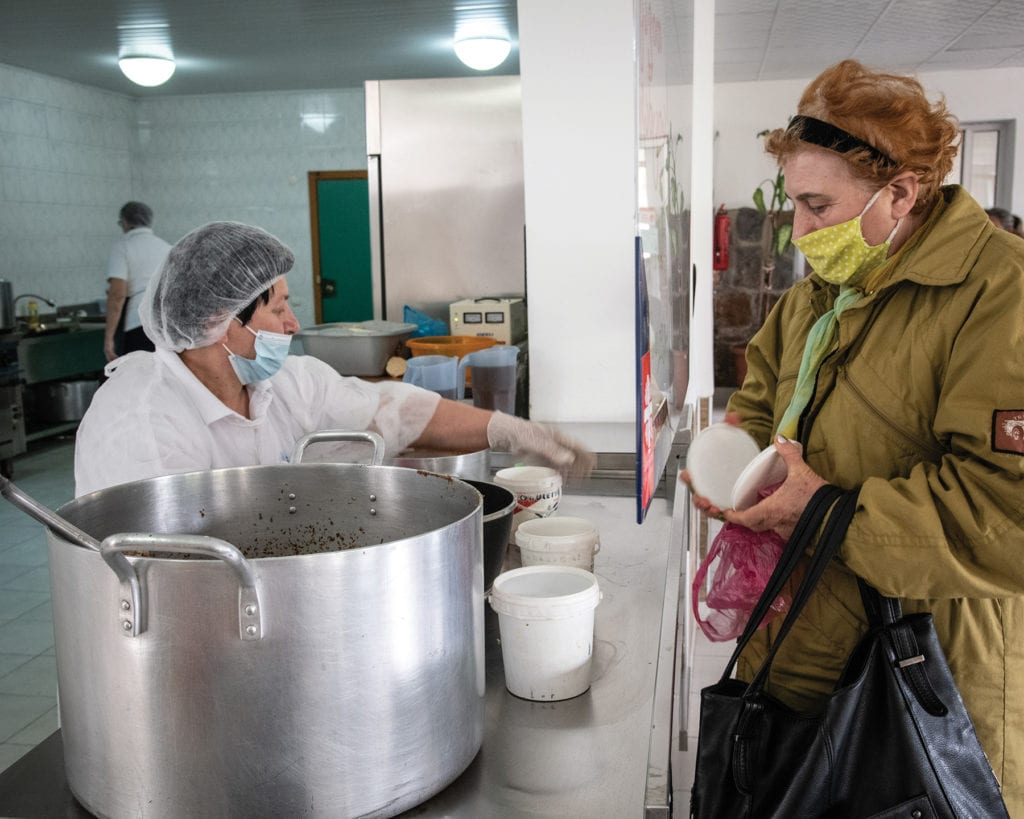 a woman in a mask collects food at the soup kitchen in Kutaisi, Georgia.