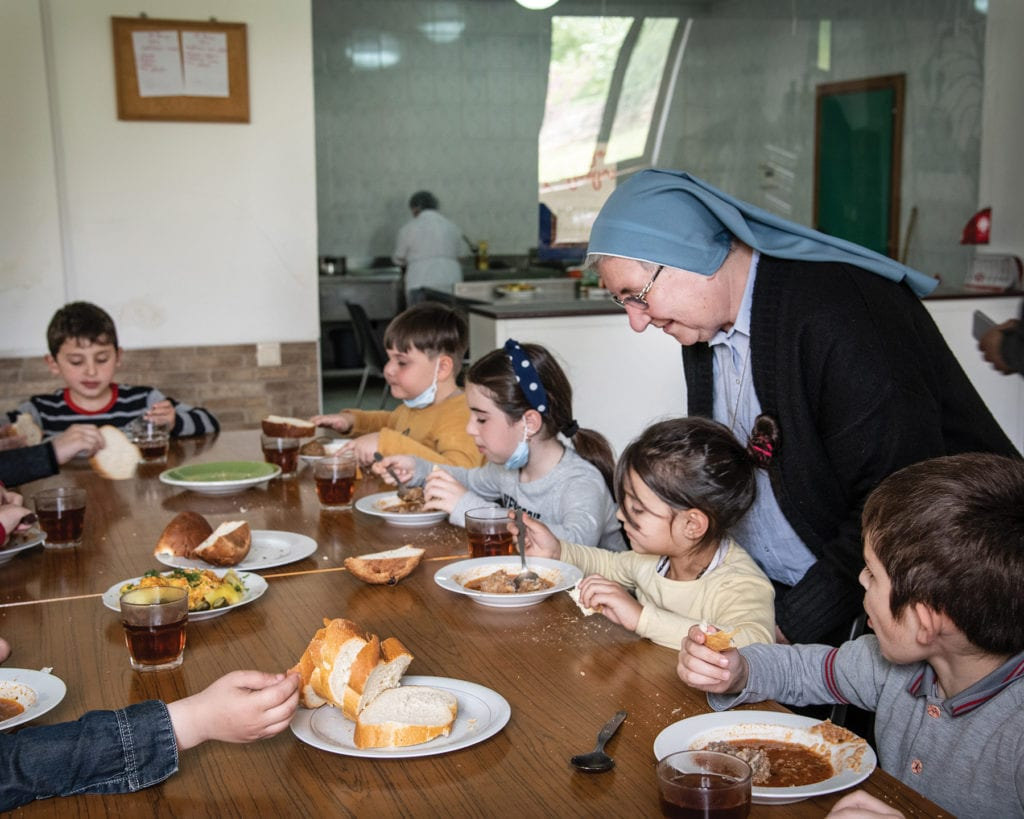a nun chats with children eating soup at a large table.