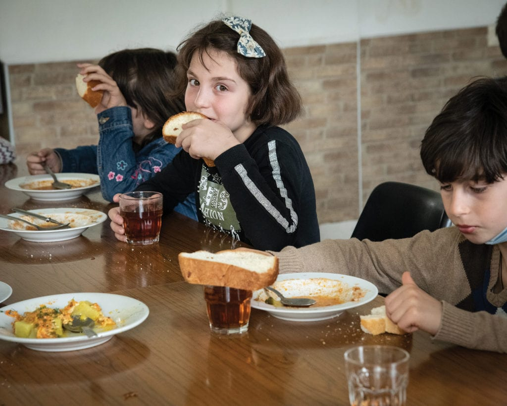 a girl eats bread with her soup at a large table.