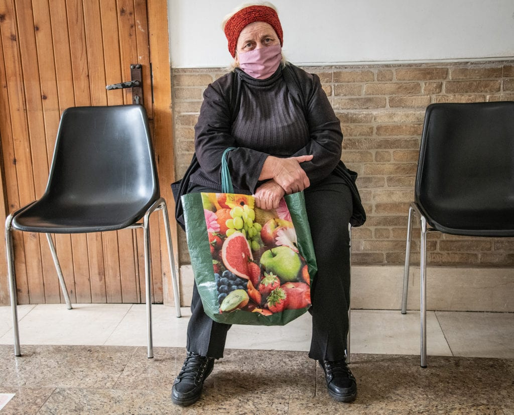 a woman with a mask and a bag is seated near a wall in the caritas soup kitchen.