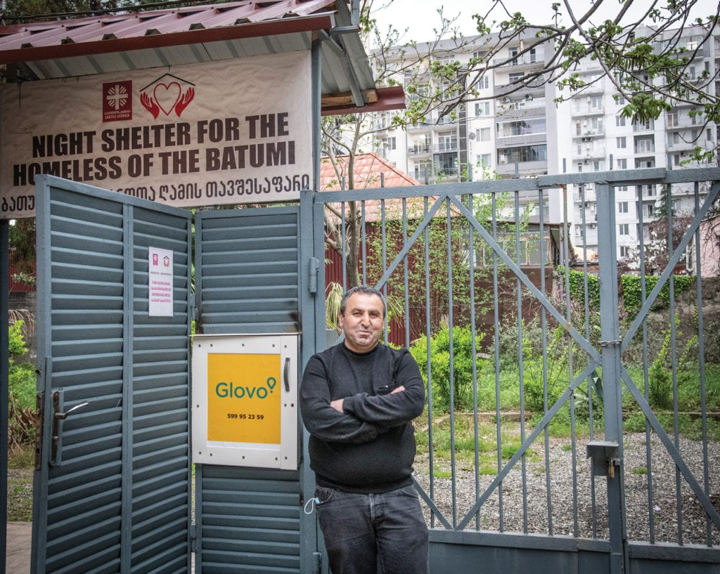 a man stands in front of the gate for the shelter in Batumi, Georgia.