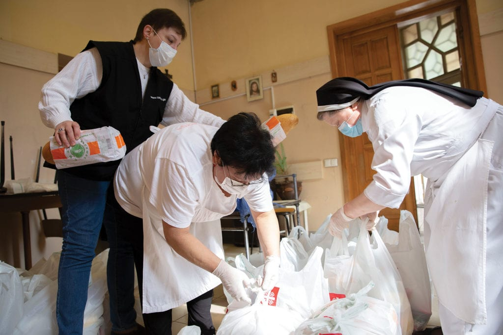 a nun and two caritas staff members tie up bags of food.