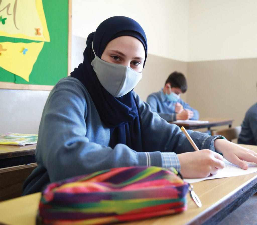 a masked student attends class in Lebanon.