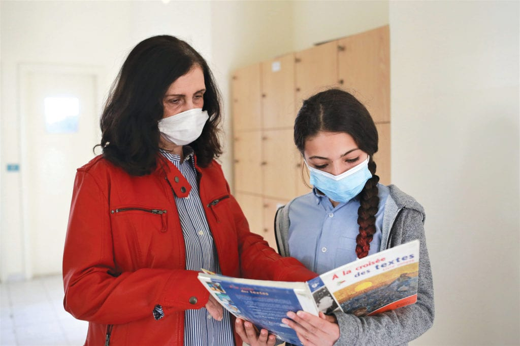 a woman and a girl look at a textbook together.