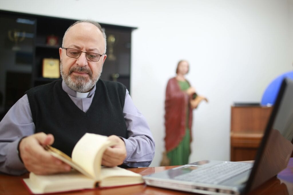 Father André Ghaoui thumbs through a theology book in the library of St. John the Apostle Seminary in Harissa, Lebanon.