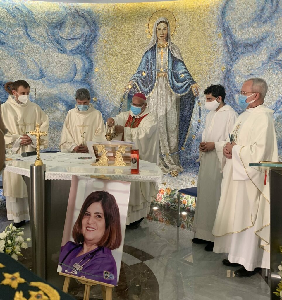 CNEWA president Monsignor Peter Vaccari, far right, is among the concelebrants of a Mass at the Rosary Sisters Chapel at Geitaoui Hospital in Beirut. Bishop Cesar Essayan, the Latin-rite bishop of Beirut, presides as the main celebrant. The woman in the portrait is Jacqueline, a 60-year-old hospital nurse who died as a result of the explosion.