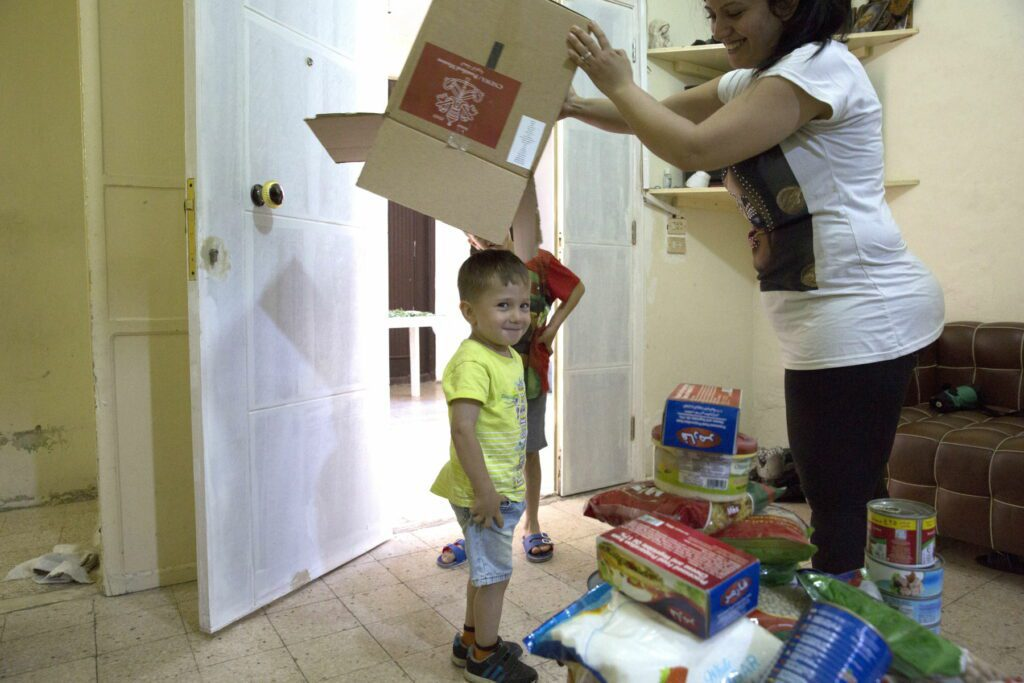 Mrs. Chahine and her two sons play with an empty box that had contained food relief supplies.