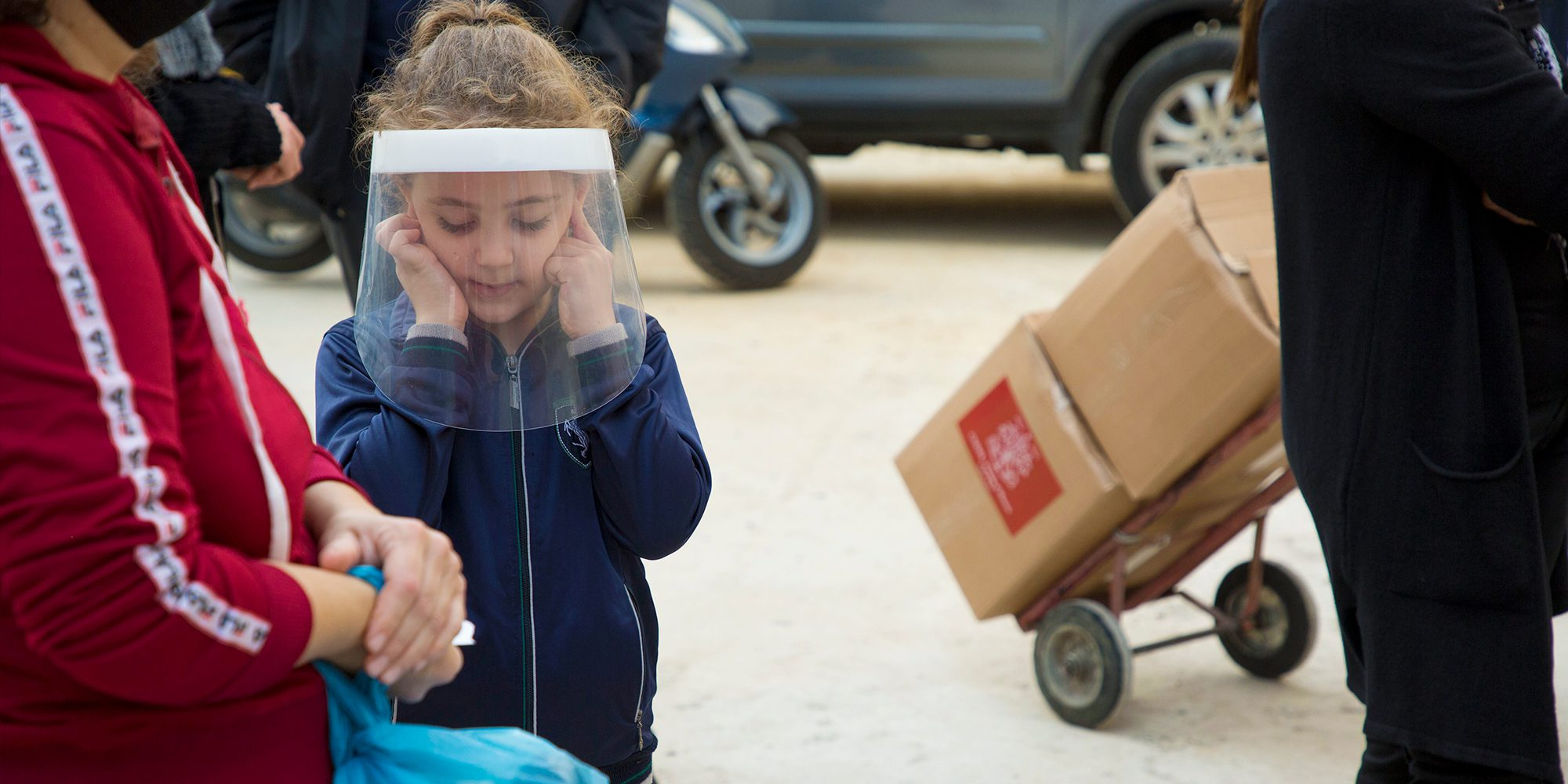 in Lebanon, a child stands in a mask while people collect food parcels distributed by CNEWA.