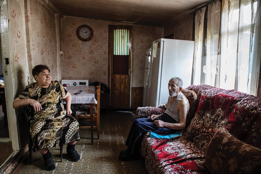 an elderly man and woman sit in a small room in a domik with a couch and kitchen appliances.