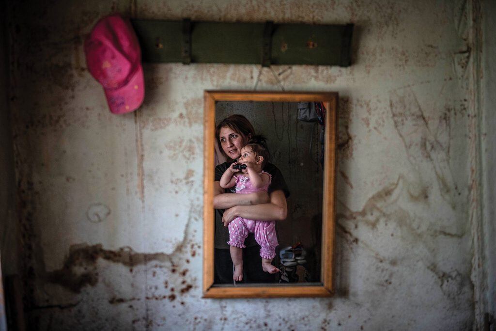 a mother and child are reflected in a small mirror on a weathered wall of a domik.