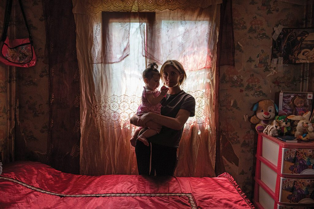 a woman holds her daughter, backlit from a curtained window in a domik.
