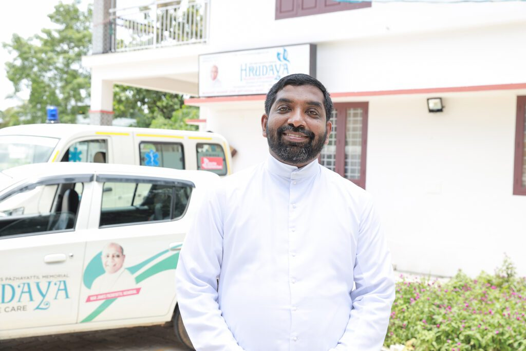 portrait of father thomas kannampilly, standing outside of the center he directs in southern india.