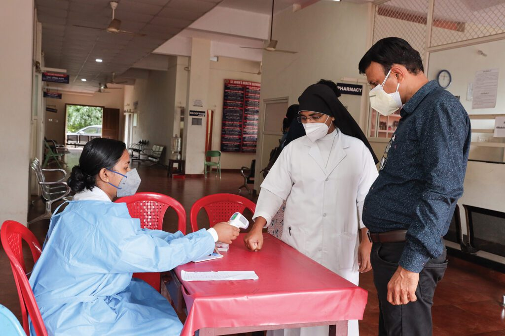 a hospital worker in southern India takes the temperature of two visitors during the pandemic.