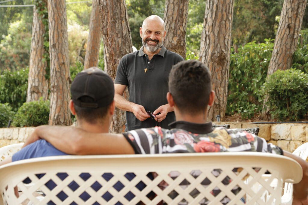 a man chats with two young men on a bench in the foreground at oum el nour.