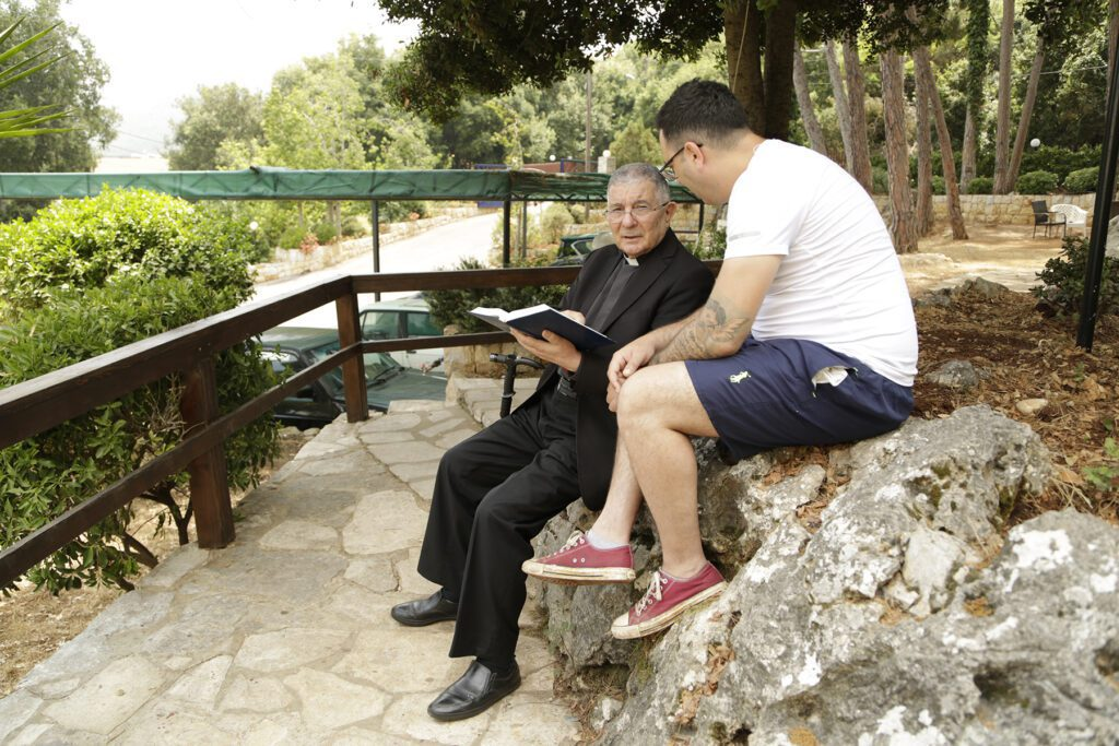 Bishop Noujaim chats with a man outside at oum el nour, both seated on a rocky retaining wall.