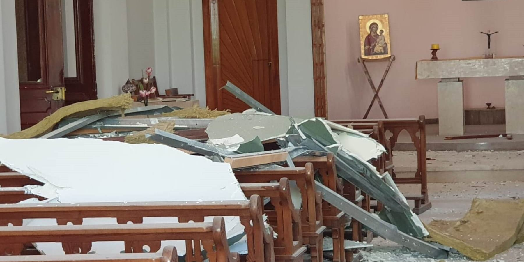 rubble fills the pews in a chapel seriously damaged by an explosion.